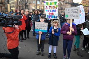 Schoolchildren holding banners in front of the media in George Square, Glasgow