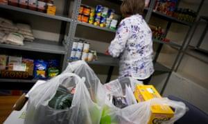 Woman filling bag in food bank.