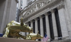 """Replicas of Arturo Di Modica's """"Charging Bull"""" are for sale on a street vendor's table outside the New York Stock Exchange."""