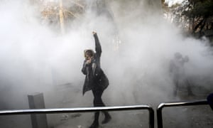 A university student protects herself from tear gas while protesting at Tehran University.