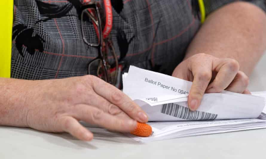 A woman counting postal votes