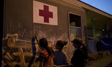 Syrian girls play next to a train wagon at the northern border point of Idomeni, Greece.