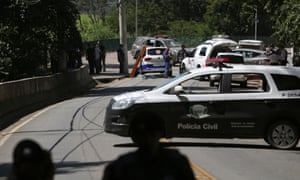 A police car blocks a road, where policemen faced a gang after attempting an armed bank robbery in Guararema, near São Paulo, Brazil, on Thursday.