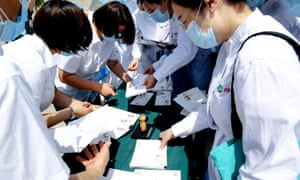 Medical workers attend an event issuing coronavirus-themed stamps on 11 May 2020 in Wuhan, China.