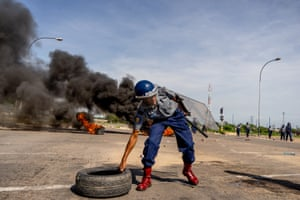 A police officer removes tyres during a 'stay-away' demonstration in the township of Emakhandeni.