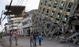 Residents walk past a row of collapsed buildings felled by the earthquake in Portoviejo, Ecuador, on Monday.