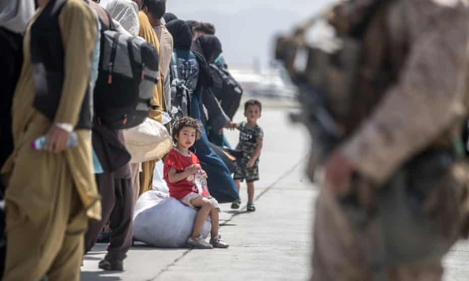 A child waits with her family to board a US air force plane during an evacuation at Kabul airport