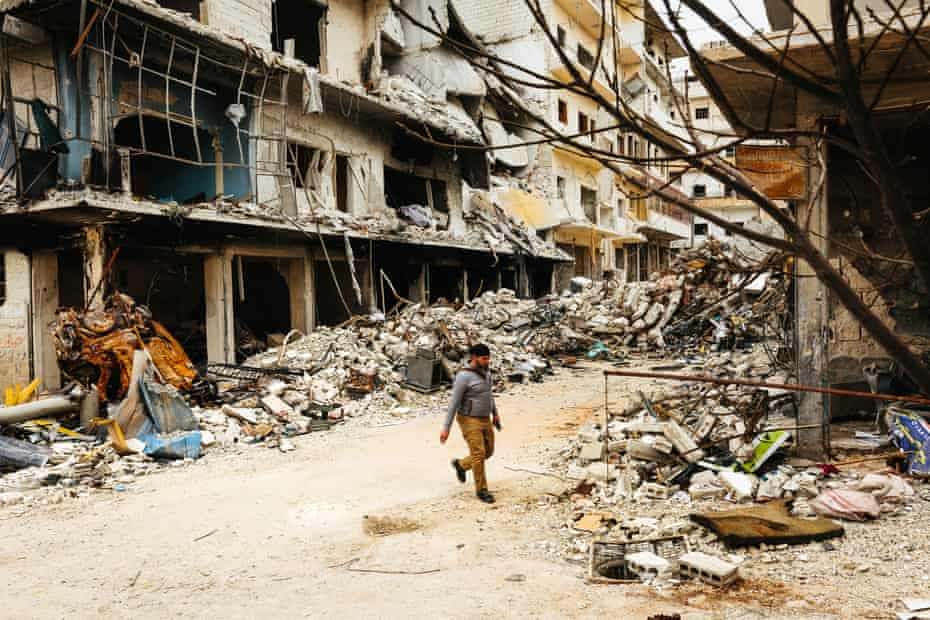 A man walks down a street lined with destroyed buildings in the town of Ariha.
