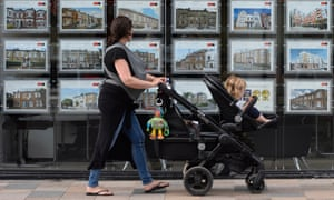 A woman looks at adverts in an estate agent window in south-west London