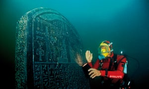 A diver under water with a stele from the site of Thonis-Heracleion that matches one from Naukratis
