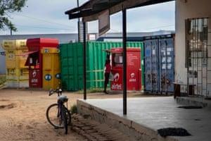 A woman opens up an ntembe mobile money kiosk in Kalomo, Zambia