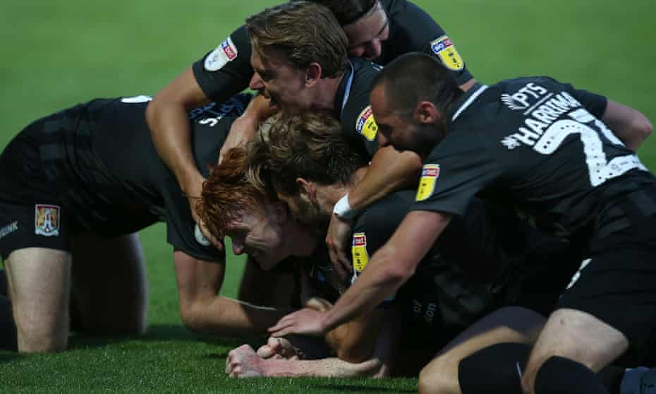 Northampton's Callum Morton is mobbed by his teammates after turning round the tie at Cheltenham with his side's third goal.