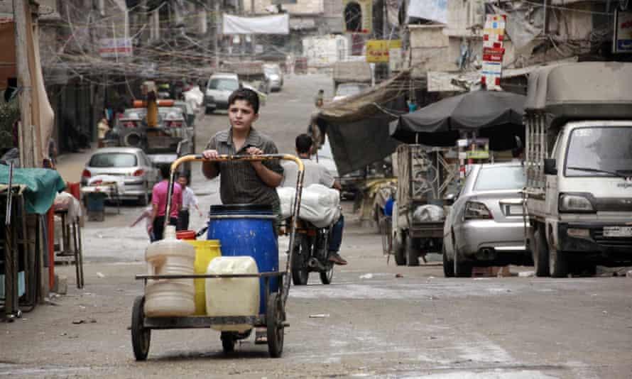 Suriyeli bir çocuk 2014'te Halep'te içi su dolu bidonlarla bir arabayı itiyor.