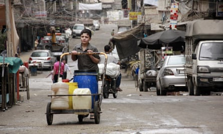 A boy pushes a cart with jerry cans filled with water in Aleppo. Syria where water shortages are thought to have contributed to the start of the civil war