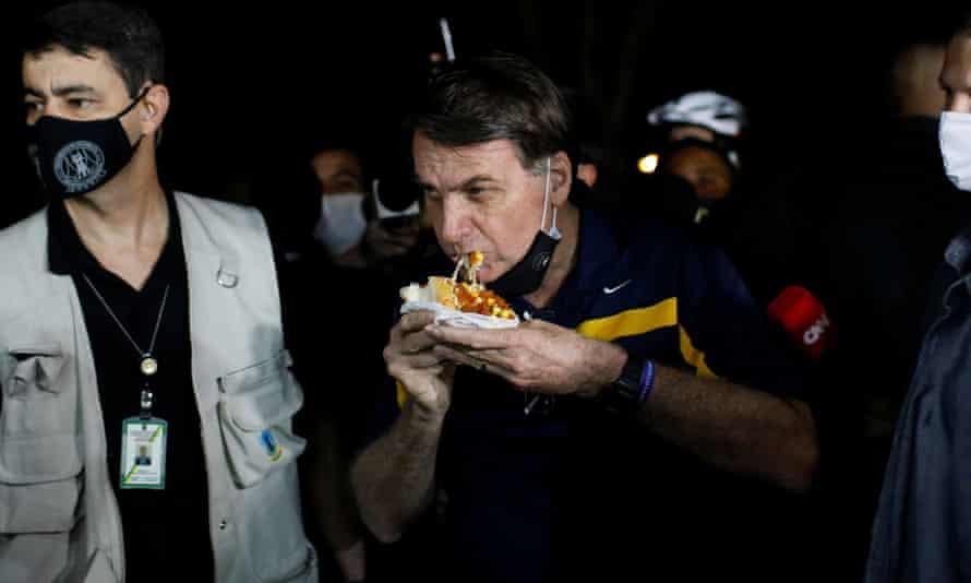 Jair Bolsonaro eats a hot dog in a street cafeteria in Brasilia