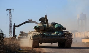 Syrian government forces' tanks drive in the village of Tal Jabin, north of the embattled city of Aleppo.