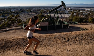 A woman runs next to a pumpjack in Los Angeles.