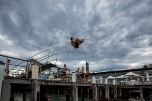 A boy jumps into the water from Manly Wharf in Sydney, Australia