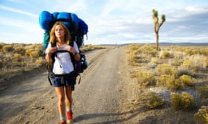 Reese Witherspoon walking alone along a path in the wilderness, a rucksack on her back, in the film Wild