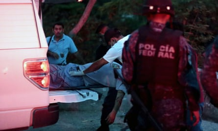 Forensic personnel carry the corpse of a person murdered by hitmen into a van in Acapulco, Guerrero.
