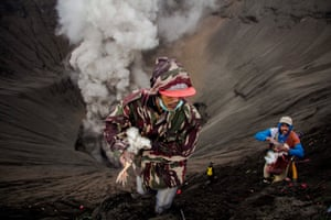 An Indonesian villager catches a chicken which was thrown by Hindu worshippers as an offering during the Yadnya Kasada festival at the crater of Mount Bromo
