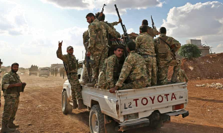 """Turkish-backed Syrian fighters near Aleppo on October 7, 2019. - US forces in northern Syria started pulling back from areas along the Turkish border ahead of a feared military invasion by Ankara that Kurdish forces say would spark a jihadist resurgence. The Kurdish-led Syrian Democratic Forces said in a statement that """"US forces withdrew from the border areas with Turkey"""" in northeast Syria. (Photo by Nazeer Al-khatib / AFP) (Photo by NAZEER AL-KHATIB/AFP via Getty Images)"""
