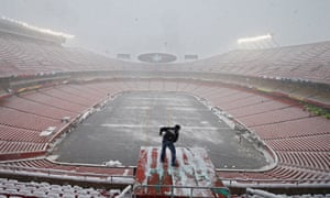 An NFL cameraman clears snow at Arrowhead Stadium in Kansas City before the Chiefs-Colts game.
