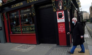 A man wearing a protective face mask walks past a closed pub amid the coronavirus outbreak, in Dublin, Ireland 1 October 2020.