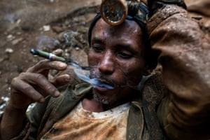 A miner resting as he smokes a cigar at a ruby mine in Mogok, north of Mandalay