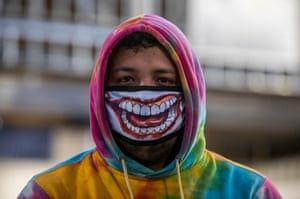 A man wears a face mask depicting a toothy grin in Managua, Nicaragua