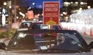 A man holds a sign in support of Amazon workers unionizing in Bessemer, Alabama, in Seattle, Washington, on 20 February.
