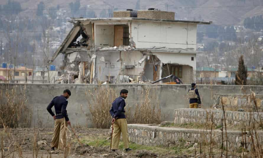 Policemen standing guard near the partially demolished compound where Osama Bin Laden was killed.