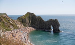 Dorset, UK: a police helicopter flies above a packed beach at Durdle Door, near Lulworth.