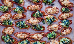 A platter full of stuffed sundried tomatoes with green and pale yellow fillings alternately