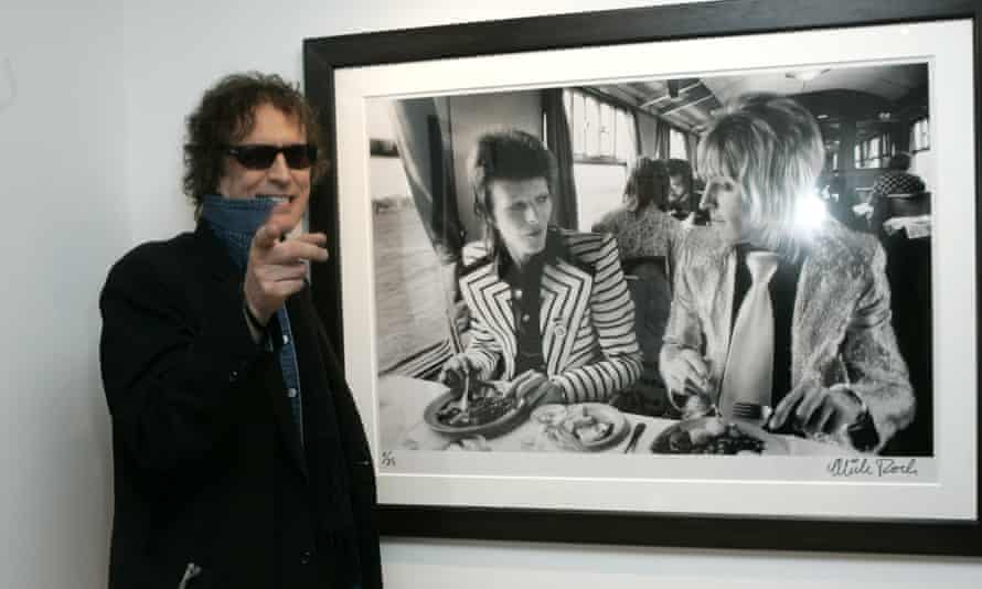 Mick Rock with his famous photo of David Bowie and Mick Ronson.