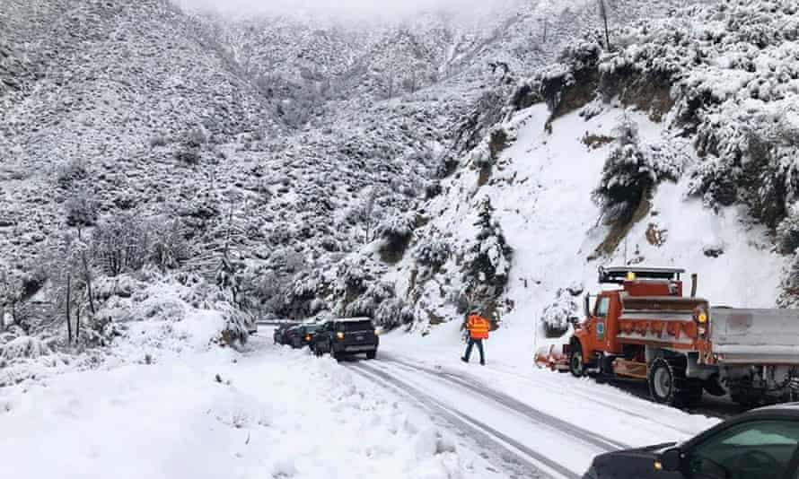 Cars stranded due to snowfall on the Angeles Crest highway are assisted by a Caltrans crew in California on 28 November.