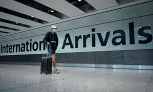 A traveller wearing a face mask walks through international arrivals at Heathrow airport with a suitcase