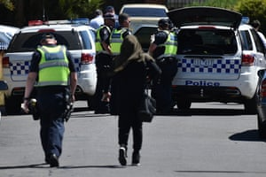 Police accompany a woman wearing a hijab as they attend the scene where a house was raided in Meadow Heights in Melbourne