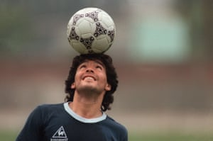 Maradona balances a football on his head as he walks off the practice field following a team session in Mexico City during the 1986 World Cup