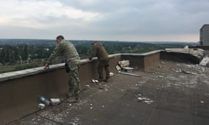 Sergei Veremeyenko, left, looks out over separatist positions from the top of an apartment block in Avdiyivka.