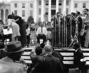 """Martin Luther King Jr waiting to be introduced at the Alabama Capitol after leading the fifty-four mile march from Selma to Montgomery, 1965'They told us we wouldn't get here,' King told the crowd of 25,000 supporters on 25 March, 1965. 'And there were those who said that we would get here only over their dead bodies. But all the world today knows that we are here, and we are standing before the forces of power in the state of Alabama saying: """"We ain't gonna let nobody turn us around""""'"""