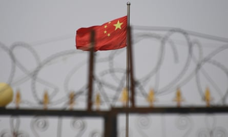 Chinese flag behind razor wire at a housing compound