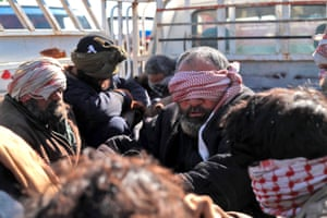 Alleged Isis fighters who fled the frontline Syrian village of Baghuz, near the Iraqi border, after being taken into custody by SDF forces