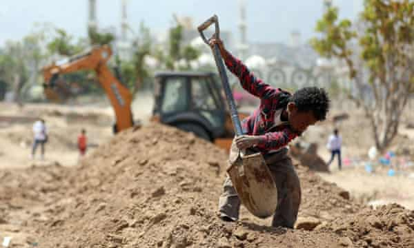 A Yemeni boy digs at a cemetery in Taiz. Yemen is facing a second wave of Covid.
