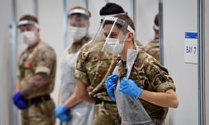 British soldiers in PPE help to administer rapid Covid-19 tests during a pilot for community testing in Liverpool