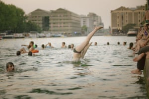 Groups of swimmers dive into and swim in the canals of Paris, France, at dusk. In 2012 a Facebook group, Laboratoire des baignades urbaines expérimentales (Laboratory of Experimental Urban Swimming), called to unite people in collective splashes during hot weather in Paris. This then led to the formation of an unofficial Paris wild swimming group, which swims – illegally, and often at night – in Parisian canals.