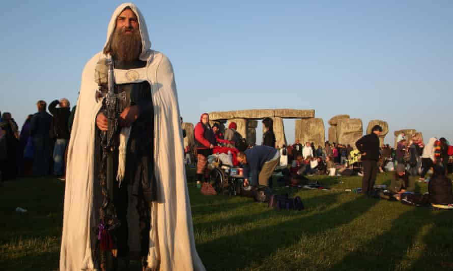 Merlin the druid stands as the sun rises at Stonehenge on the summer solstice.