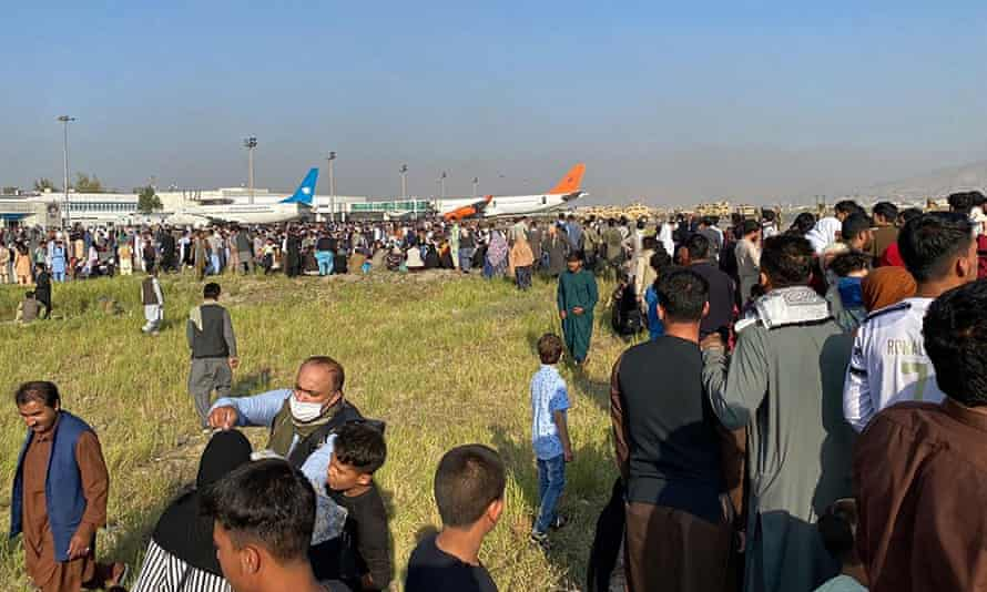 Afghan passengers crowd at the airport as they wait to leave from Kabul