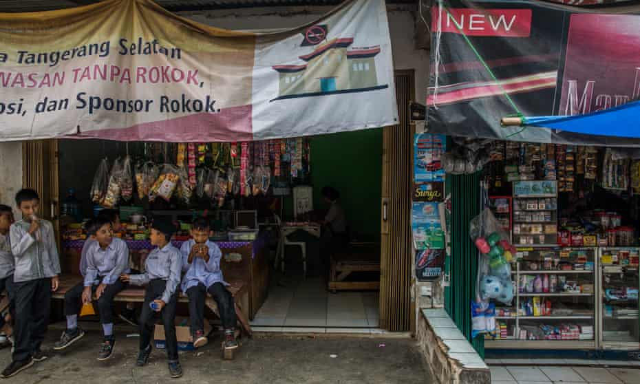 Indonesian schoolchildren at a food stall with an anti tobacco banner, next to stalls with cigarette advertising and products on sale opposite thei school.