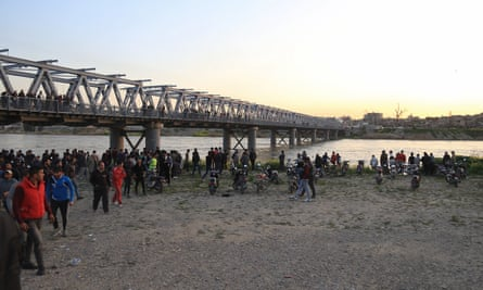 People wait on the bank of the Tigris near where the ferry sank